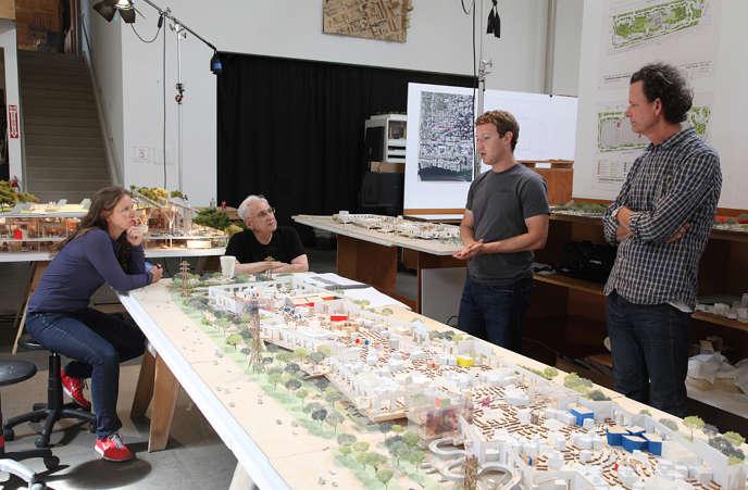 Sur cette image fournie par Facebook en 2013, Frank Gehry (en noir) et Mark Zuckerberg (debout à sa gauche) examinent la maquette du bâtiment MPK 20.