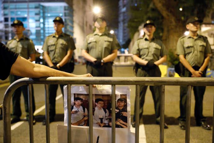 Un manifestant tenant la photo des trois opposants à l'emprise du régime chinois condamnés, le 17 août, à des peines de prison ferme à Hongkong, le 18 août.