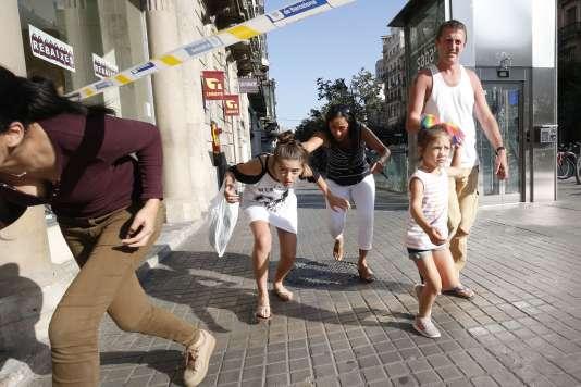 Des passants se mettent à l'abri après l'attaque terroriste, à Barcelone, le 17 août.