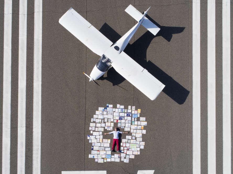 Il photographie, entre autres, des collectionneurs au côté de leur collection. La sienne est constituée de 400 consignes de sécurité de compagnies aériennes. Pour cet autoportrait, il s'aide d'undrone, sur la piste d'un aérodrome à Florence.