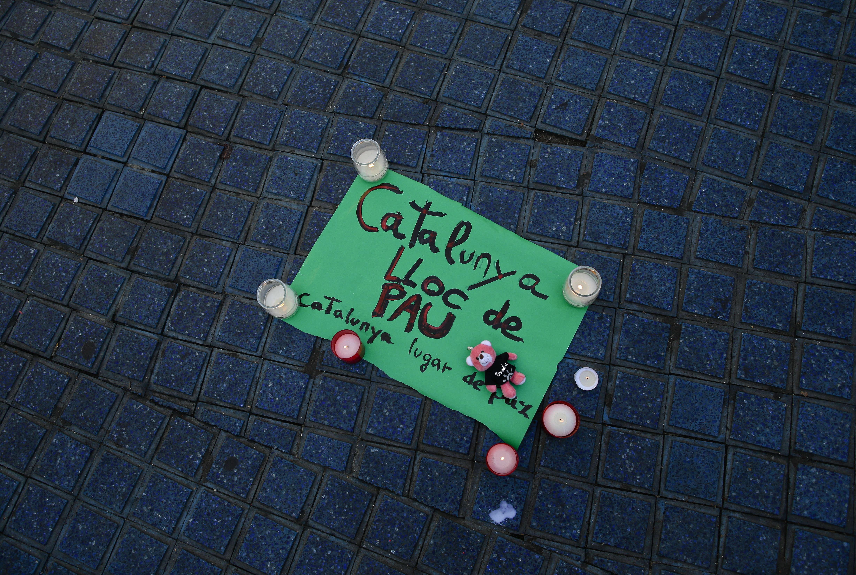 Une petite affiche sur laquelle est écrit : «Catalogne –lieu de paix» est placé avec des bougies sur un trottoir des Ramblas.