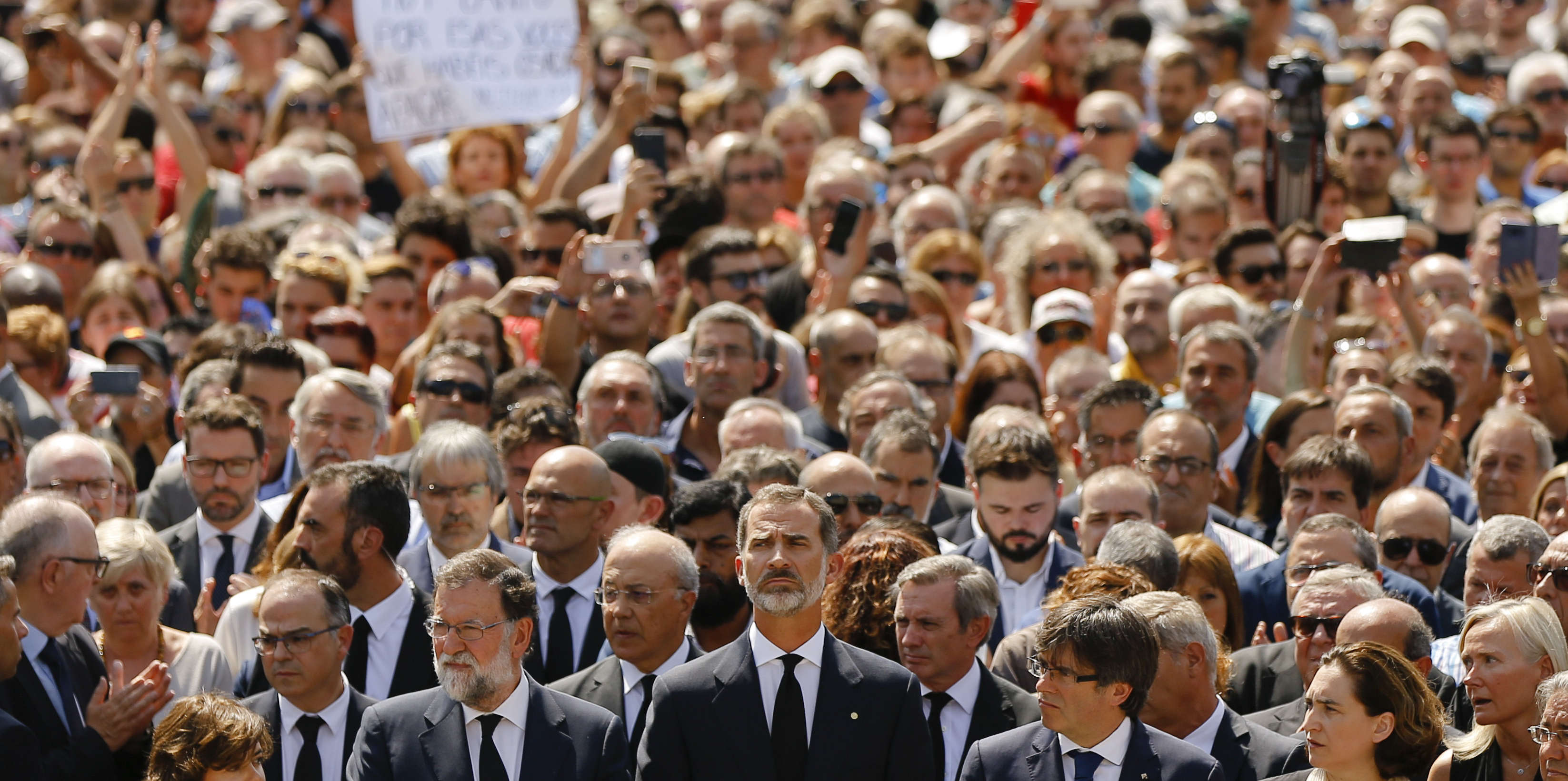 King Felipe of Spain, center, Prime Minister Mariano Rajoy, center left, and and Catalonia regional President Carles Puigdemont, center right, join people observing a minute of silence in memory of the terrorist attacks victims in Las Ramblas, Barcelona, Spain, Friday, Aug. 18, 2017. Spanish police on Friday shot and killed five people carrying bomb belts who were connected to the Barcelona van attack that killed at least 13, as the manhunt intensified for the perpetrators of Europe's latest rampage claimed by the Islamic State group. (AP Photo/Francisco Seco)