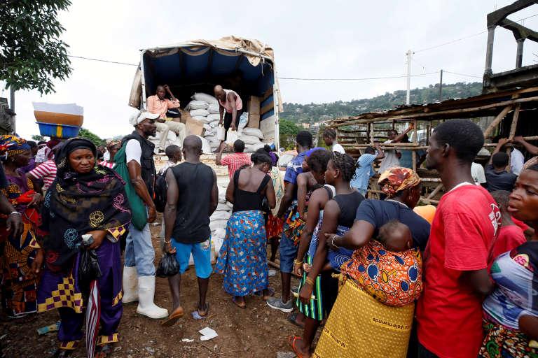 Des personnes déplacées par les coulées de boues torrentielles attendent de recevoir des produits de première nécessité, à Freetown, le 18 août.