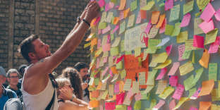 A man is sticking post it on a kiosk where the attack happened.