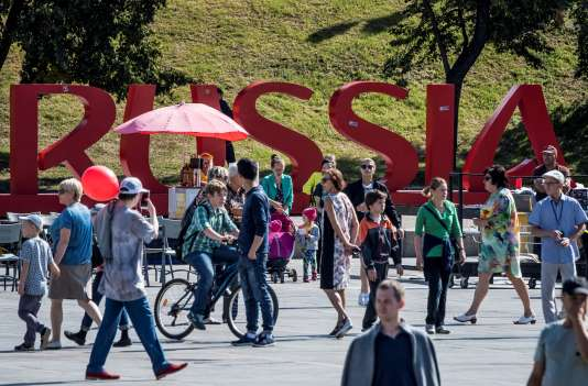 """People walk past a giant sign reading """"Russia 2018"""" in downtown Yekaterinburg, on August 19, 2017. The city of Yekaterinburg will host several games of the FIFA World Cup 2018. / AFP PHOTO / Mladen ANTONOV"""