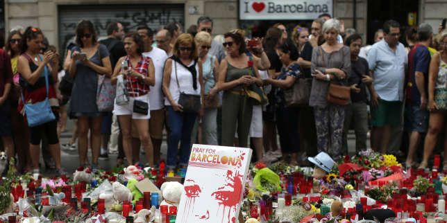 People stand next to candles and flower tributes placed on the ground after a terror attack that killed 14 people and wounded over 120 in Barcelona, Spain, Sunday, Aug. 20, 2017. Police put up scores of roadblocks across northeast Spain on Sunday in hopes of capturing a fugitive suspect at large following the vehicle attack. (AP Photo/Manu Fernandez)