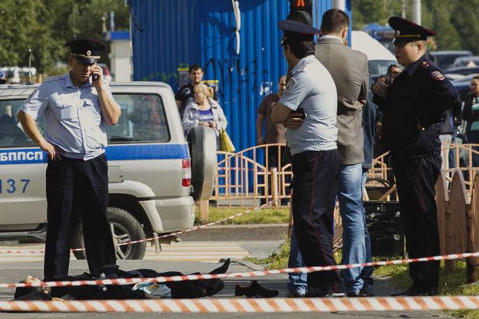 Des policiers autour du cadavre de l'assaillant, tué après avoir attaqué plusieurs personnes avec un poignard, à Sourgout, le 19 août.