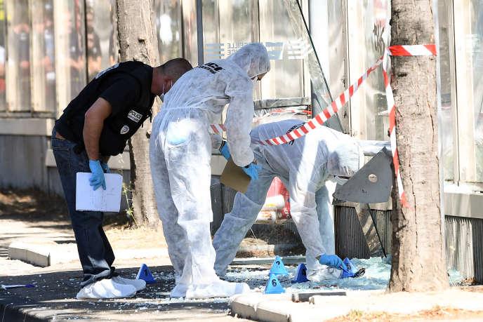 Un officier de la brigade criminelle et des membres de la police scientifique travaillent sur l'un des Abribus touchés, le 21 août, à Marseille.