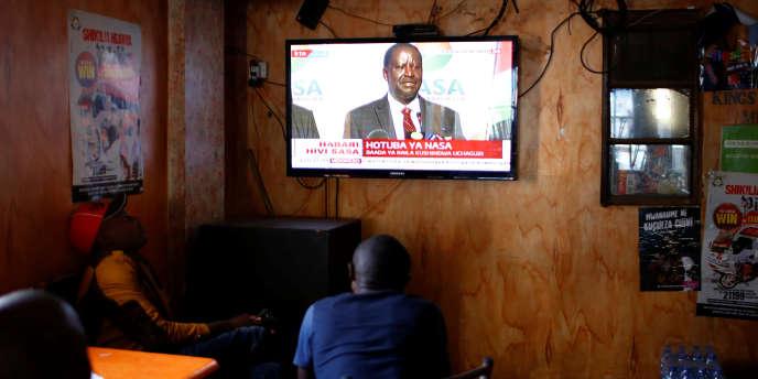 Dans le bidonville de Mathare, à Nairobi, des hommes regardent à la télévision la conférence de presse du chef de l'opposition, Raila Odinga, le 16août 2017.