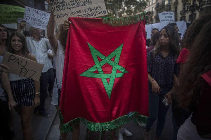 Une jeune femme brandit un drapeau marocain lors de la marche de la communauté musulmane contre le terrorisme, à Barcelone le 21 août.