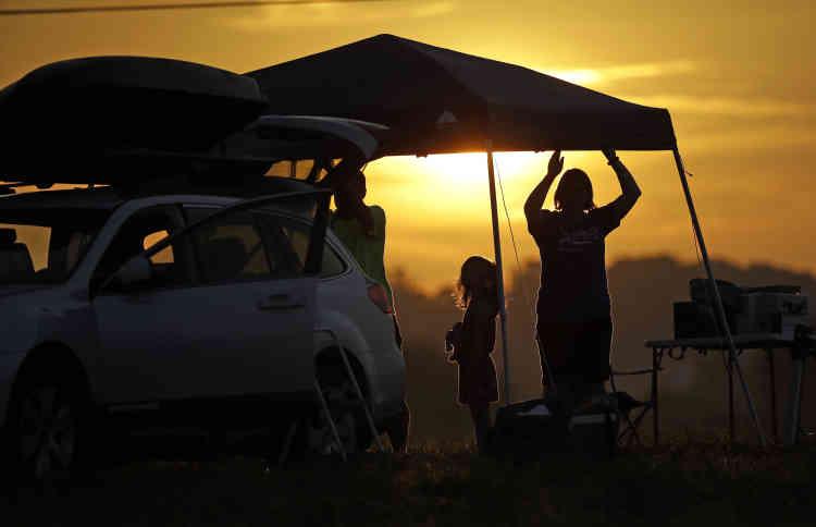 Une famille installe une tente dans un camping pendant le lever du Soleil, à OrchardDale, près de Hopkinsville (Kentucky).L'emplacement se situe sur le tracé de la plus grande obscurité.