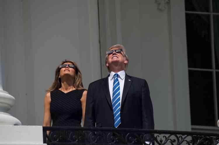 Le président américain Donald Trump et sa femme Melania admirent l'éclipse depuisle balcon de la Maison Blanche.