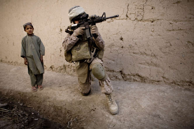 Un enfant afghan aux côtés d'un Marine durant une patrouille au sud de Kaboul (Afghanistan), le 3 novembre 2010.
