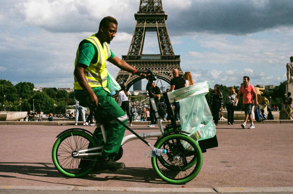 Shaka, agent de la propreté de Paris sur un vélo-collecteur Kiffi, ramasse détritus et papiers gras au milieu des touristes, au pied de la tour Eiffel et au Trocadéro, le 19 août vers 16h30.