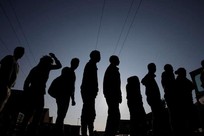 Des migrants d'Ethiopie et d'Erythrée font la queue lors de la distribution de nourriture près de l'ancienne« jungle» de Calais, le 23 août 2017.