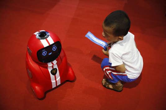Un enfant regarde un robot « intelligent» capable d'auto-apprentissage à la World Robot Conference de Pékin, le 23 août 2017.