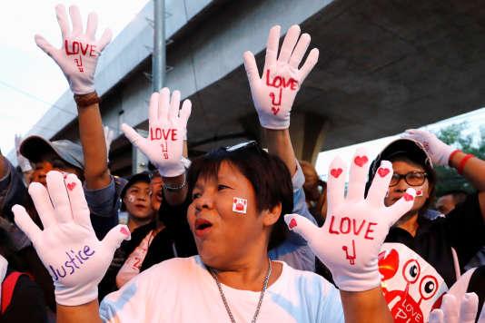 Des partisans deYingluck Shinawatra, le 25 août à Bangkok. Sur les gants, le mot« pou» (crabe), le surnom donné par sa famille à l'ex-première ministre.