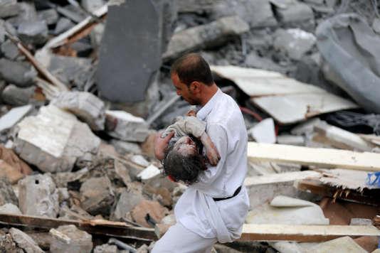 Un homme porte le corps d'un enfant retrouvé sous les décombres d'une maison détruite lors d'un raid aérien de la coalition saoudienne, à Sanaa, le 25 août 2017.
