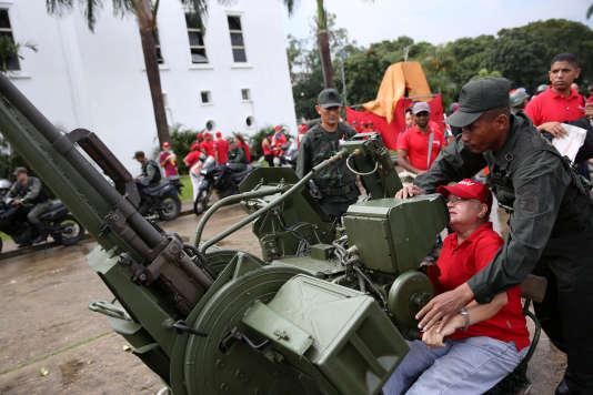Un membre des forces armées bolivariennes explique le fonctionnement d'une canon anti-aérien lors de manoeuvres militaires organisées à Caracas, le 26 août.