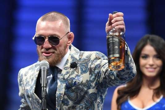 Conor McGregor répond aux questions des journalistes après sa défaite, une bouteille de whiskey à la main, le 26 août.