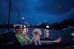 A rescue helicopter hovers in the background as an elderly woman and her poodle use an air mattress to float above flood waters from Tropical Storm Harvey while waiting to be rescued from Scarsdale Boulevard in Houston, Texas, U.S. August 27, 2017. REUTERS/Adrees Latif