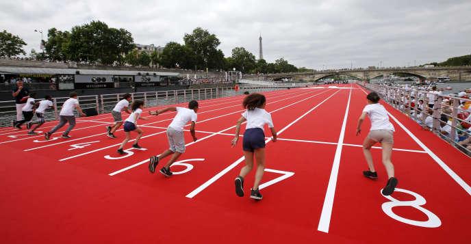 Des enfants prennent le départ d'un 100 mètres sur une piste d'athlétisme installée sur la Seine à Paris, le 23 juin.