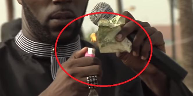 Kémi Séba brûlant un billet de 5000francs CFA, le 19août 2017, à Dakar.