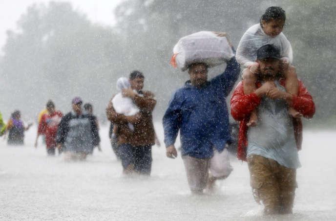Des sinistrés fuient leurs habitations, à Beaumont Place, dans le Texas, le 28 août.