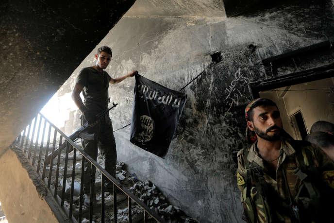 Un membre des Forces démocratiques syriennes retire un drapeau de l'organisation Etat islamique, à Rakka, le 14 août.
