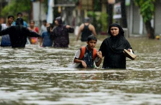 Une mère ramène son fils de l'école, dans une rue inondée de Bombay, en Inde, le 29 août.