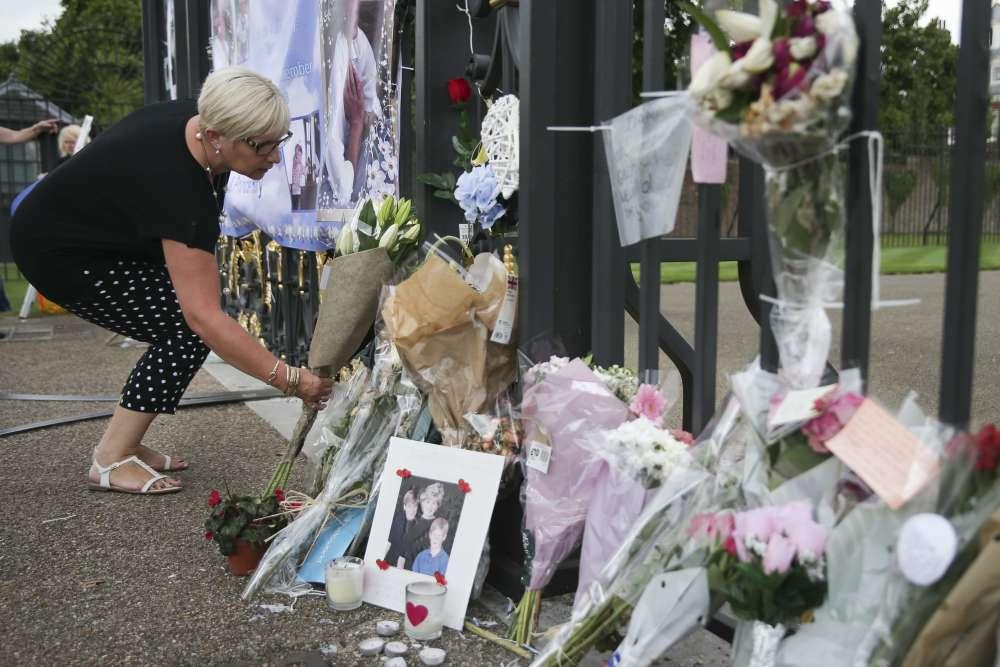 Une femme dépose des fleurs devant les portes du palais de Kensington, à Londres, où résidait la princesse, le 29août.