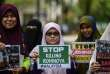 Women hold up placards during a protest against the persecution of Muslim ethnic minority Rohingya in Myanmar, in Kuala Lumpur on August 30, 2017. Hundreds of protesters from Myanmar demonstrated in Malaysia on August 30 against renewed violence in their homeland that has forced thousands of members of the Muslim ethnic minority Rohingya to flee. / AFP / MOHD RASFAN