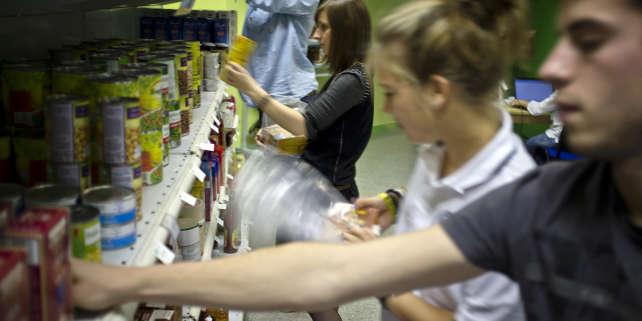 Des étudiants disposent des produits sur les rayonnages d'une épicerie solidaire, le 7 novembre 2011 à Villeurbanne, sur le campus de l'université de Lyon-I.