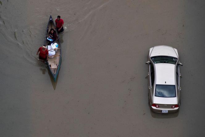 Des habitants de Houston, au Texas, se déplacent en canoë, jeudi 31 août 2017.