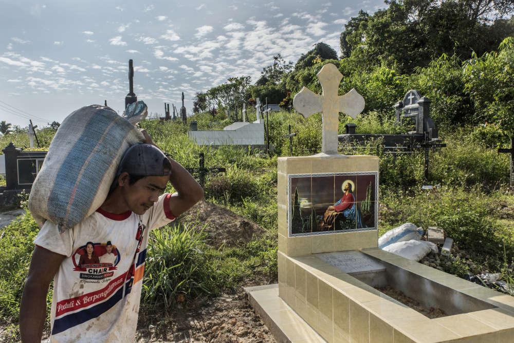 Un Dayak au travail dans un cimetière chrétien de Singkawang. Les Dayak, habitants originels, ont été convertis au christianisme mais ils conservent des pratiques religieuses ancestrales.