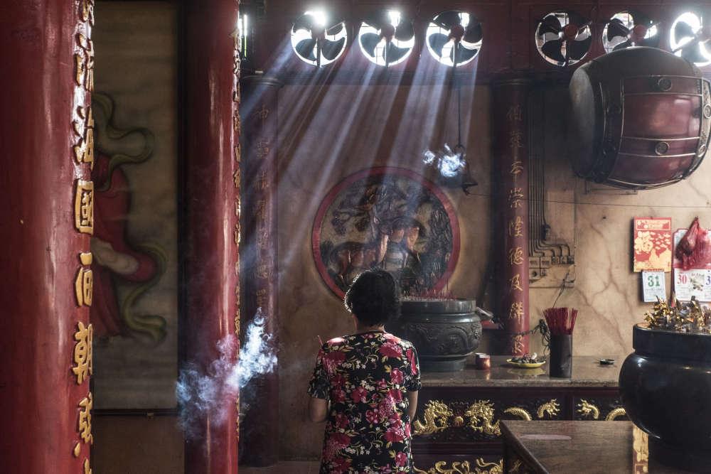 Une femme, bâtons d'encens en offrande à la main, vient prier au temple Tri Dharma Bumi Raya, le plus ancien temple chinois de Singkawang (Kalimantan occidental).