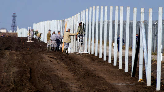 Des prisonniers hongrois construisent une clôture contre le passage de migrants, près du village de Gara, à la frontière serbo-hongroise, le 27 octobre 2016.
