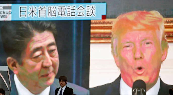Un homme passe devant téléviseur de rue montrant le premier ministre japonais Shinzo Abe et le président américain Donald Trump dans un bulletin d'information sur leur conférence téléphonique au sujet de la menace de la Corée du Nord, à Tokyo, au Japon, le 3 septembre.