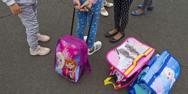 Students stand with their school bags in the playground at Pierre Mendes France primary school in Clermont-Ferrand at the start of the new school year on September 4, 2017.  / AFP / Thierry Zoccolan