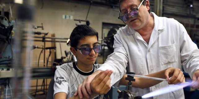 Un salarié (à droite) donne des instructions à un jeune travailleur dans une entreprise de gravure sur verre, le 29 juin 2012 à Joinville-le-Pont, près de Paris.
