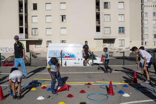 Deux éducateurs de l'« Urban sport truck » proposent des activités sportives aux jeunes de la cité des Rosiers, à Marseille, le 10 août.