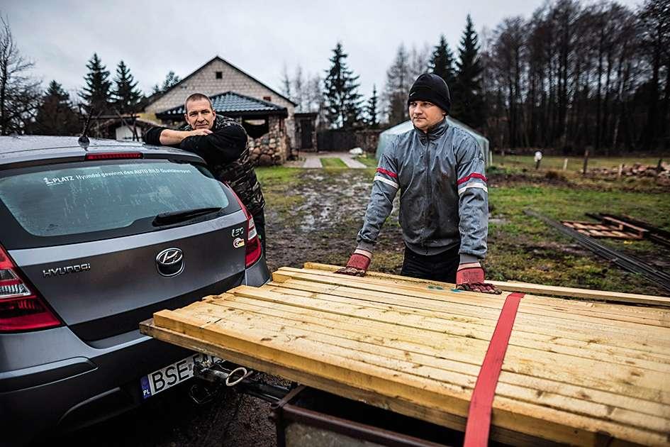 Deux hommes chargent le bois restant après avoir terminé la construction d'une grange.