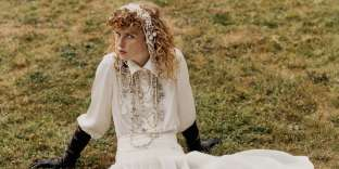 Blouse en satin et jupe plissée en tweed irisé. Colliers en perles, perles de verre et strass, Chanel. Gants en cuir, Causse. Cuissardes en cuir verni, Mulberry.