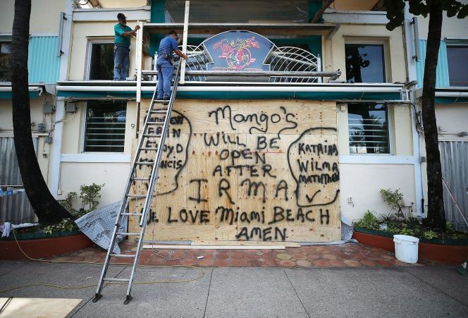 Des ouvriers s'affairent à protégerle restaurant Mango's à Miami Beach, alors que l'ouragan Irma approche, le 7 septembre 2017.