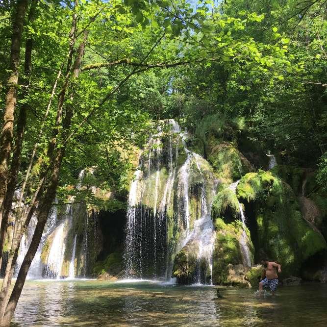Près d'Arbois, la Cascade des Tufs se cache au fond de la reculée des Planches. L'eau, chargée de calcaire dissout, sculpte une forme en éventail, couverte de mousses.