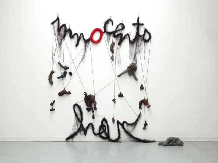 """«Invitée à concevoir une œuvre pour l'exposition, Annette Messager a réalisé une grande installation murale composée du mot """"Innocents"""", dont le """"O"""" renvoie au cri du tableau de Poussin, et du mot """"help""""ainsi que de divers fragments de corps en tissu et plastique recouverts de résine.»"""
