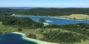 Vue sur le lac du Grand Maclu et le lac d'Ilaydepuis le Belvédère des Quatre Lacs. Les «blancs»qui bordent l'eau sont constitués de carbonate de calcium.Il faut marcher plus d'une heure sur lesentier qui part du village de La Chaux-du-Dombief pour admirer ces paysages grandioses.