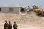 Un bulldozer détruit la maison d'un Palestinien, sous la surveillance de soldats israéliens, au sud d'Hébron, en Cisjordanie, le 14 août.