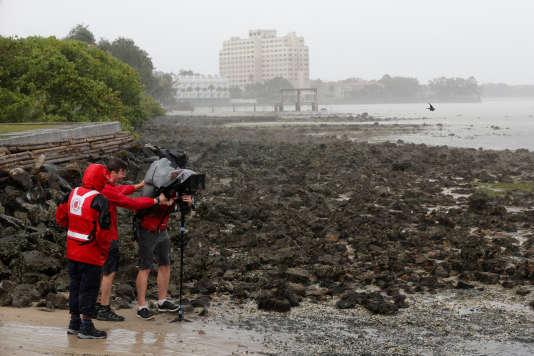 Une équipe de journalistes à Tampa (Floride) filme le port dont l'eau s'est retirée, quelques minutes avant l'arrivée de l'ouragan Irma, le 10 septembre.