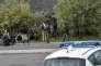 Des policiers surveillent des migrants installés sur un bord de route, aux abords de Calais (Pas-de-Calais), le 16 août.